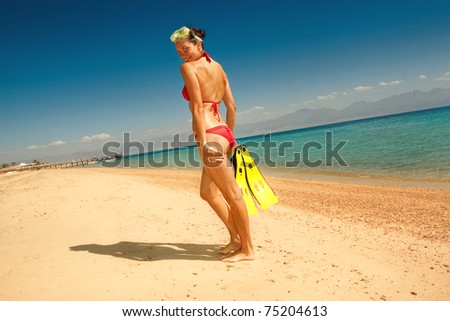 girl in a red bikini with a mask and flippers on beach - stock photo