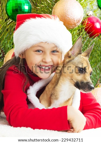 girl in a red Christmas dress hugging dog on the background of the Christmas tree - stock photo