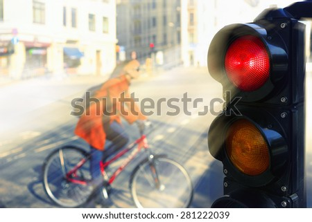 Girl in a red coat on a bicycle at the intersection of the city for a red traffic light in spring day - stock photo