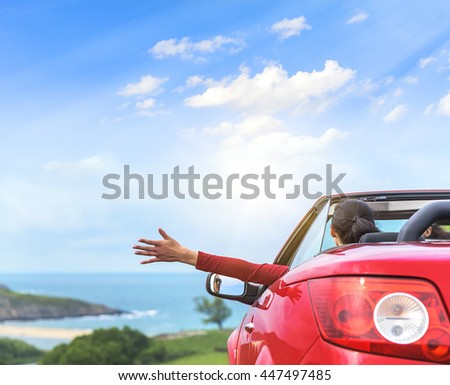 Girl in a red convertible car on a background seascape.