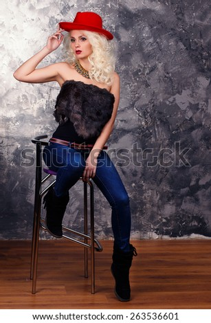 girl in a red cowboy hat sitting on a high chair.The blonde in a cowboy's hat on a dark background - stock photo