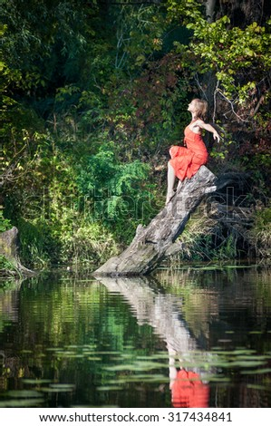 girl in a red dress lying on an old tree trunk.