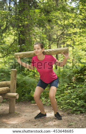 Girl in a red shirt and blue shorts playing sports outdoors.