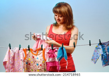 girl in a red T-shirt hanging on a rope baby clothes. clothes dryer. check the quality of the clothes