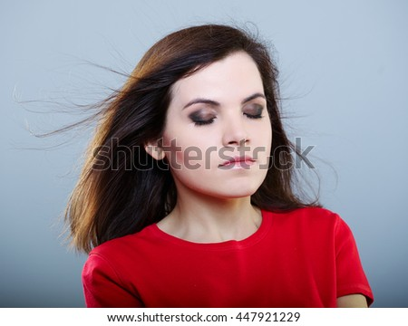 girl in a red T-shirt with flying hair and closed eyes is holding neck hands on a gray background