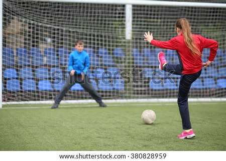 Girl in a red tracksuit throws the ball into the goal with boy keeper - stock photo