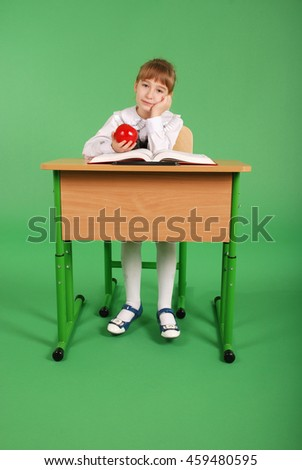 Girl in a school uniform sitting at a desk and reading a book isolated on green background