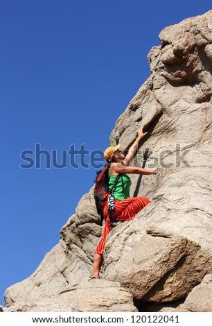 girl in a skirt climbs on a rock, Egypt, Dahab - stock photo