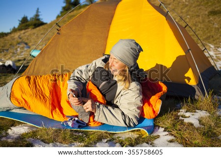 Girl in a sleeping bag lying near the tent and looks at the phone.