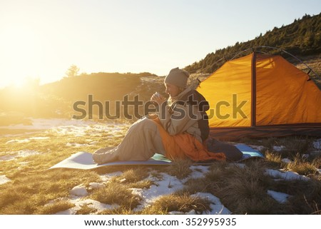 Girl in a sleeping bag sitting near the tent and was holding the Cup.