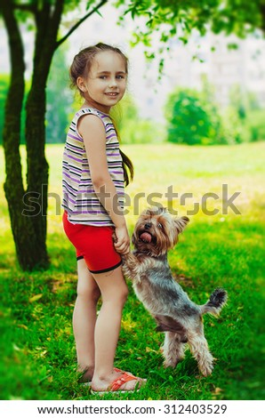girl in a striped sweater smiles and holds a small dog