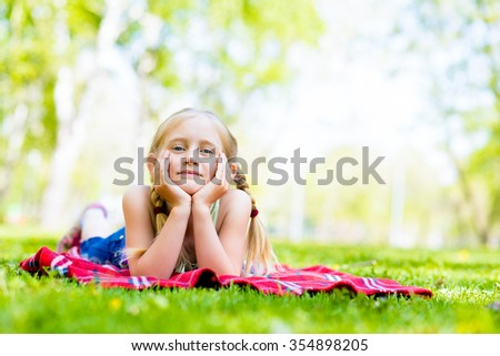 girl in a summer park lies on the rug on the grass - stock photo