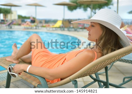 girl in a sun lounger by the pool - stock photo