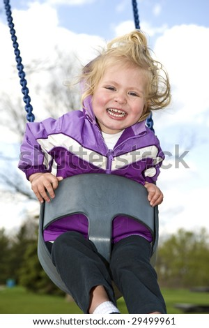 Girl in a toddler swing - stock photo