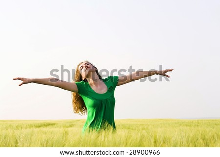 girl in a wheat field enjoying the open air - stock photo