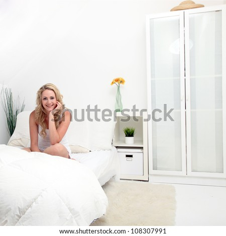 Girl in a white bedroom Friendly smiling attractive girl in a white bedroom with minimalistic modern decor relaxing sitting on her bed - stock photo