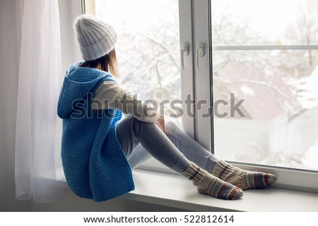 Amazing Girl In A White Hat And Blue Vest Is Sitting On The Windowsill
