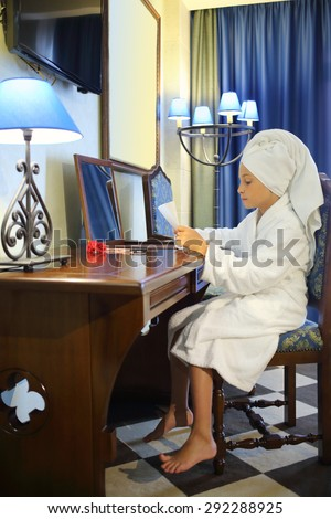 Girl in a white robe and towel on head sitting at a dressing table with a sheet of paper in hands - stock photo