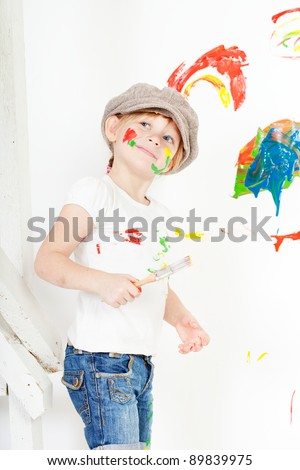 girl in a white T-shirt and a cap bedaubed with bright paints - stock photo