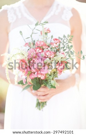 girl in a white wedding dress holding a bouquet of pink flowers  - stock photo