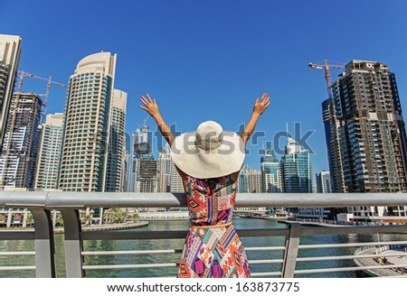 Girl in a wide-brimmed hat standing on the bridge and looks at the Dubai Marina - stock photo