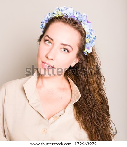 Girl in a wreath of flowers in studio - stock photo