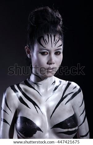 Girl in Airbrush Body Paint with Zebra skin art in Black background, low key studio lighting - stock photo