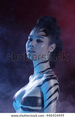 Girl in Airbrush Body Paint with Zebra skin art in Black background, low key studio lighting, blue red gel color with smoke - stock photo