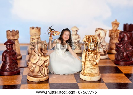 Girl in alice in wonderland dress shrunken to miniature size of a chess piece - stock photo