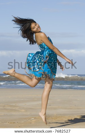Girl in asian inspired dress jumping into the air - stock photo