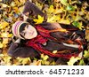 Girl in autumn yellow leaves. Outdoor. - stock photo