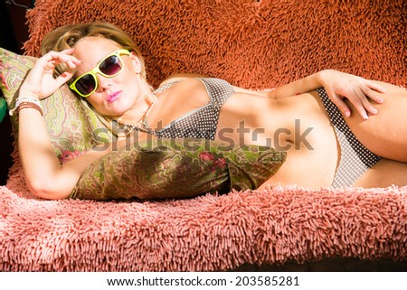 Girl in bathing suit and sunglasses lying on the couch and tans