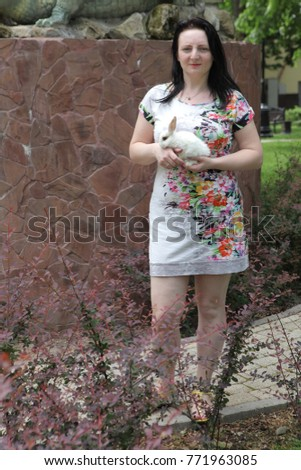 girl in beautiful dress holding a live white rabbit