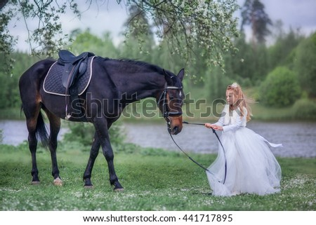 Girl in beautiful white dress with black horse in blossom garden  - stock photo