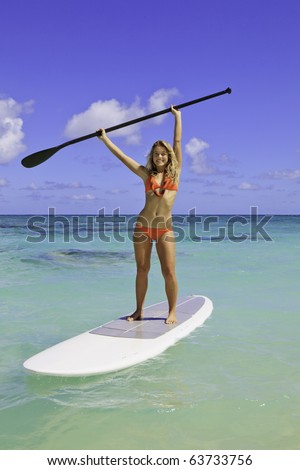 girl in bikini on a stand up paddle board in hawaii