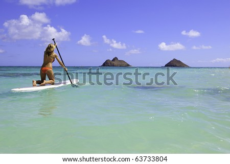 girl in bikini on a  stand uppaddle board in hawaii