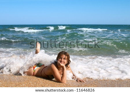 girl in bikini sunburning in the waves on sand beach
