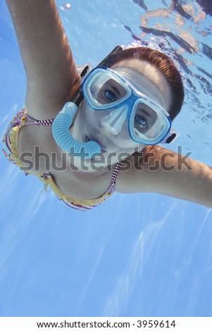 Girl in bikini swimming underwater in blue pool - stock photo