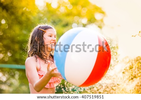 Girl in bikini with ball at the sprinkler, summer - stock photo
