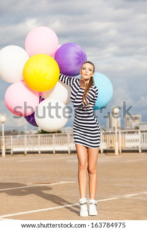 girl in black and white striped short dress and white high top sneakers sends air kiss holding bunch of multicolored balloons - stock photo