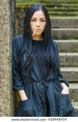 Girl in black coat and standing outdoor and smoking a cigarette