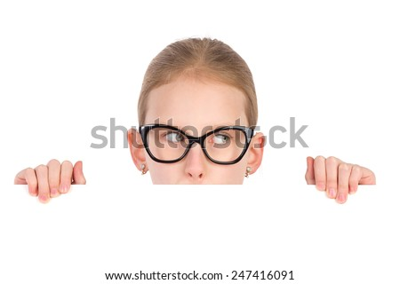 Girl in black glasses peeking behind white placard and looking away. Studio portrait isolated on white.