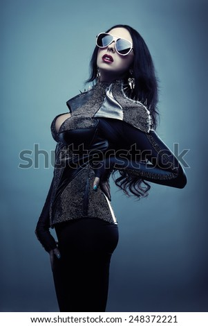 girl in black posing on a blue background - stock photo