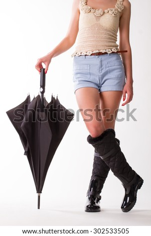 Girl in black rubber boots with umbrella standing on a white background.Summer girl. - stock photo