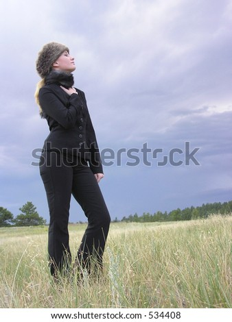 girl in black with fur hat standing in a field
