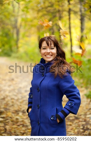 Girl in blue coat at autumn park - stock photo