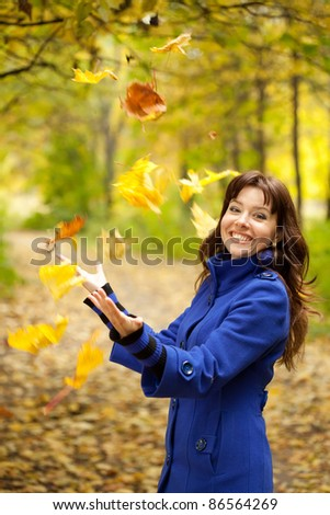 Girl in blue coat throw up maple leaves