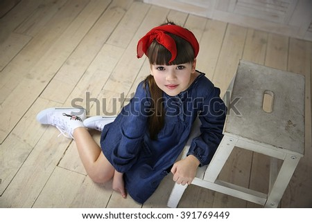 Girl in blue dress and red bow, sitting on white chair near a wardrobe - stock photo