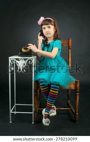 Girl in blue dress talking on old phone - stock photo