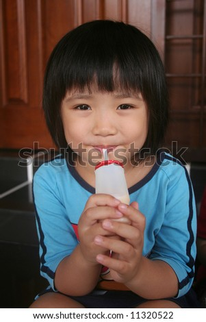 Girl in blue enjoy drinking yogurt drink - stock photo